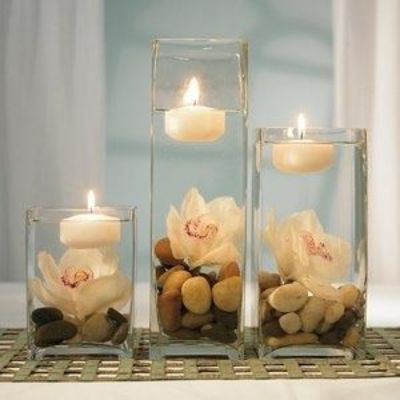 Underwater orchid centerpiece with square vase and floating tealight. Very simple do do this yourself, and you can replace the rocks at the bottom with glass beads, shells or sand depending on the theme of your wedding.