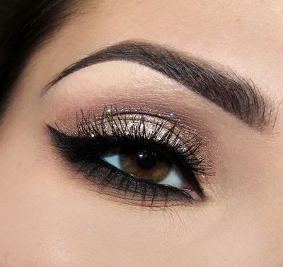 Gold glitter eye shadow on lid and dark shadow under lower lashes.