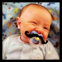 winking baby with a mustache pacifier -