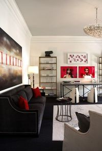 Dillard Design Group Chic, elegant black & red modern living room design with black velvet Hollywood regency sofa with nailhead trim, gray ceiling, red silk pillows, red & black abstract art, gray rug, gold bookcases and red art.