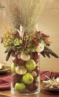 For a stunning multi-level arrangement, combine fresh flowers, seasonal fruits and dried materials. Select autumn's classic forms: field-grown wheat, pumpkins, Indian corn, apples and fall flowers. Center the small cylinder vase inside the larger one....