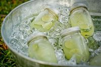 Lemonade in mason jars with slices of lime in a galvanized bucket. fun!