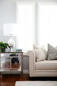 Belmont Design Group Gorgeous living room with blue gray walls paint color, mirrored chest with black granite top, mercury glass lamp, camel linen rolled arm sofa with nailhead trim, gray pillows and ivory wool rug.