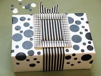 Black circles cut from labels add graphic punch to this gift wrapping via Dsharp.