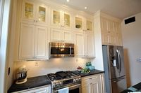 upper glass cabinets; tall cabinet over fridge; honed granite countertops