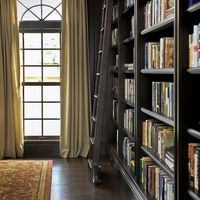 Replace existing windows with floor to ceiling windows, add bookcases along length of the wall.