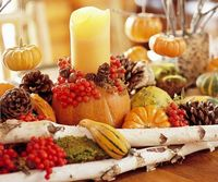 Carve a hole in a pumpkin to fit a pillar candle, then hot-glue pinecones and berries around the hole as a decorative ring