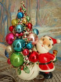 Vintage Holt Howard Santa candle holder circa 1958 holds a vintage snow-tipped bottle brush tree decorated with vintage ornaments and glass beads from vintage garlands.
