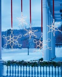 Outdoor Hanging Snowflake Ornaments Hand-twist rope lights, using our template as a guide to create glimmering oversize ornaments. Hang them from their cords (disguised with ribbon) at varying heights along a porch or under the eaves of the house.